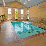 magnificen-small-indoor-swimming-pool-with-gorgeous-blue-tile-base-and-magnifceint-brick-wall-and-grabiet-paving-with-exquisite-armchair-for-class-house-style